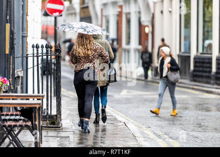 London, UK - September 12, 2018: Back of people, woman, women walking with umbrellas in rainy city weather on sidewalk by cafe crossing street, wet ro - Stock Photo