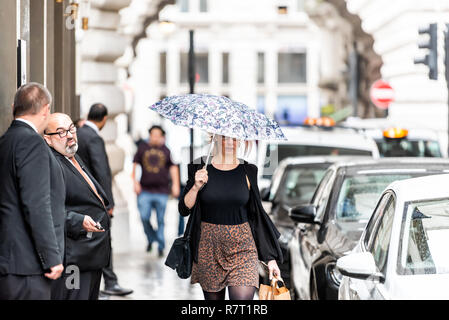 London, UK - September 12, 2018: Woman, business people, businessman, businessmen walking standing with umbrella in rainy city weather on sidewalk by  - Stock Photo
