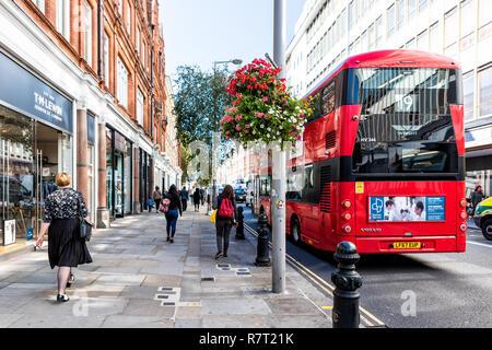 London, UK - September 13, 2018: Neighborhood district of Chelsea, street, red double decker bus, TM Lewin retail store, flower decorations, people wa - Stock Photo