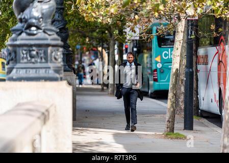 London, UK - September 14, 2018: Young African American happy businessman man walking in Vauxhall neighborhood on Albert Embankment sidewalk by buses - Stock Photo
