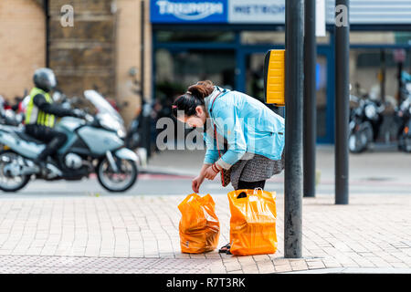 London, UK - September 14, 2018: Neighborhood district of Pimlico with woman and orange Sainsbury's grocery supermarket bags on street sidewalk road d - Stock Photo