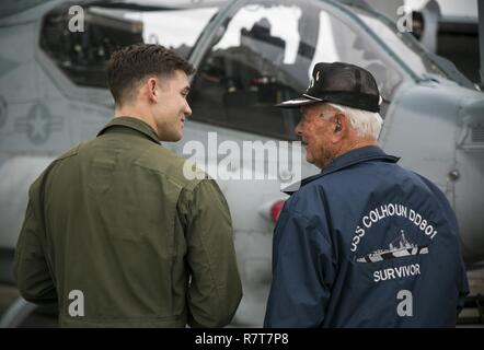U.S. Marine Capt. Joe Hamlin gives Donald Irwin, a United States Navy World War II veteran, a tour of the Bell AH-1Z Super Cobra, April 7, 2017 on Marine Corps Air Station Futenma, Okinawa, Japan. Irwin, who served aboard a number of ships during World War II, fought at Midway and Guadalcanal and survived the sinking of the USS Colhoun during the Battle of Okinawa. Irwin returned to Okinawa and exchanged stories with the Marines and Sailors stationed on the island. Irwin is a San Jose, California native, and Hamlin, a Corbin, Kentucky, native, is a Bell AH-1 Super Cobra pilot with Marine Mediu - Stock Photo