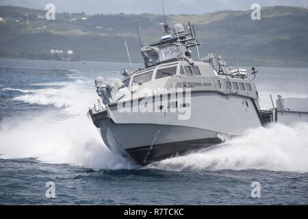 A MK VI patrol boat, assigned to Coastal Riverine Group (CRG) 1 Detachment Guam, maneuvers off the coast of Guam April 6, 2017. CRG 1 Detachment Guam is assigned to Commander, Task Force 75, which is the primary expeditionary task force responsible for the planning and execution of coastal riverine operations, explosive ordnance disposal, mobile diving and salvage, engineering and construction, and underwater construction in the U.S. 7th Fleet area of operations. - Stock Photo