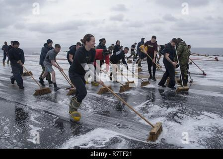 SEA OF JAPAN (April 9, 2017) Air department Sailors scrub the flight deck of the amphibious assault ship USS Bonhomme Richard (LHD 6) following an aqueous film forming foam (AFFF) countermeasure washdown. AFFF is a mixture of water and highly concentrated detergent used on the flight deck and hangar bay to smother fires. Bonhomme Richard, flagship of the Bonhomme Richard Amphibious Ready Group is on a patrol, operating in the Indo-Asia-Pacific region to enhance warfighting readiness and posture forward as a ready-response force for any type of contingency. - Stock Photo