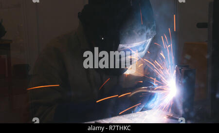 A welder in helmet doing his job. Welding process. Smoke and sparks - Stock Photo