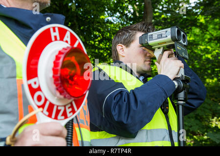 Police during speed monitoring with a laser gun or hand-held laser meter, North Rhine-Westphalia, Germany - Stock Photo