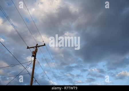 Electrical grid infrastructure, utility pole and overhead power supply lines against the blue sky and clouds in Wyoming, USA. - Stock Photo