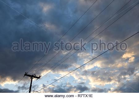 Utility pole and overhead power supply lines against the sky and clouds at sunset in Wyoming, USA. - Stock Photo
