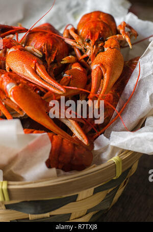Boiled crawfish with dill in wooden dish. - Stock Photo