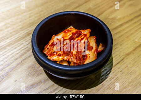 Korean Kimchi in a Small Black Bowl with Red Chili Sauce - Stock Photo