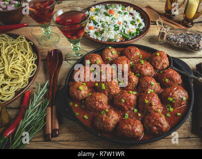 Homemade meatballs in tomato sauce. Frying pan on a wooden surface, rice with vegetables, pasta - Stock Photo