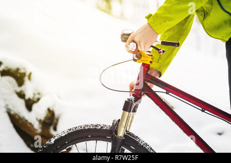 Men rider servicing an extreme bike in the field- pumping a suspension fork on a trail in the winter forest. - Stock Photo