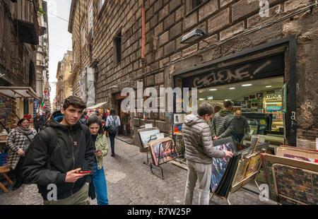 Passersby, poster stand, on Via San Biaggio dei Librai, street in Centro Storico quarter, Naples, Campania, Italy - Stock Photo