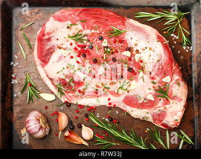 Fresh meat. Raw lamb shoulder ready for baking with garlic, rosemary, juniper, pepper and salt. Cooking a delicious dinner. Selective focus - Stock Photo