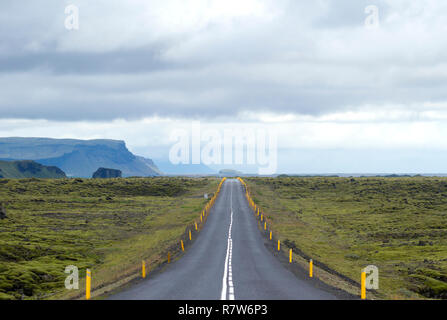 ring road route around iceland crossing an ancient lava river covered by moss with the cliffs and the sea in the background - Stock Photo