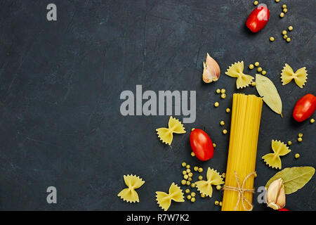 Frame for food. Pasta ingredients. Cherry tomatoes, spaghetti pasta, garlic and spices on a dark grunge background, copy space, top view - Stock Photo