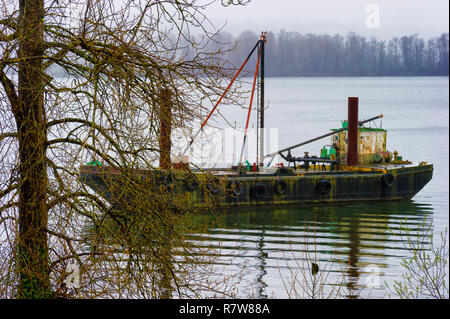 An old rusty derelict looking work boat sits anchored near the banks on the Washington State side of the Columbia River. - Stock Photo