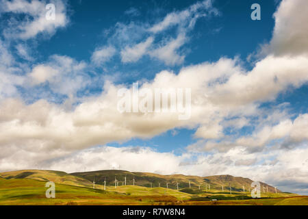 View of the Columbia Hills dotted with wind turbines under big blue skies filled with puffy white clouds from Stonehenge World War I Memorial Grounds  - Stock Photo