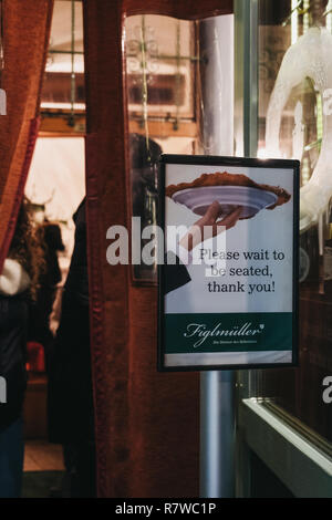 Vienna, Austria - Novermber 24, 2018: 'Wait to be seated' sign outside Figlmuller on Wollzeile restaurant in Vienna. Opened in 1905, it is often refer - Stock Photo