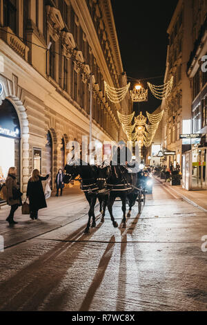Vienna, Austria - November 24, 2018: Horse carriage tour on a street in Vienna, Austria, in the evening. These tours are very popular amongst tourists - Stock Photo