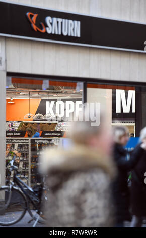 10 December 2018, North Rhine-Westphalia, Köln: Passers-by pass by a branch of the Saturn retail chain. Photo: Henning Kaiser/dpa - Stock Photo