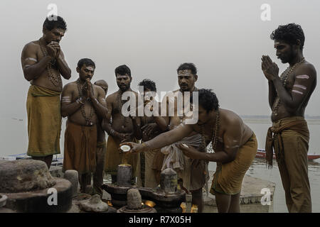 July 23, 2018 - Varanasi, Uttar Pradesh, India - Men are seen performing a Hindu ceremony on the banks of the Ganges river in Varanasi..Varanasi is a city in the northern Indian state of Uttar Pradesh dating to the 11th century B.C. Regarded as the spiritual capital of India, the city draws Hindu pilgrims who bathe in the Ganges River's sacred waters and perform funeral rites. The river is dedicated to the Hindu god Shiva. (Credit Image: © Enzo Tomasiello/SOPA Images via ZUMA Wire) - Stock Photo