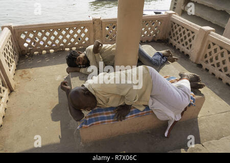 July 23, 2018 - Varanasi, Uttar Pradesh, India - Men are seen resting on the banks of the Ganges river in Varanasi..Varanasi is a city in the northern Indian state of Uttar Pradesh dating to the 11th century B.C. Regarded as the spiritual capital of India, the city draws Hindu pilgrims who bathe in the Ganges River's sacred waters and perform funeral rites. The river is dedicated to the Hindu god Shiva. (Credit Image: © Enzo Tomasiello/SOPA Images via ZUMA Wire) - Stock Photo