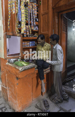 July 23, 2018 - Varanasi, Uttar Pradesh, India - Men are seen outside a store in an Old Town in Varanasi..Varanasi is a city in the northern Indian state of Uttar Pradesh dating to the 11th century B.C. Regarded as the spiritual capital of India, the city draws Hindu pilgrims who bathe in the Ganges River's sacred waters and perform funeral rites. The river is dedicated to the Hindu god Shiva. (Credit Image: © Enzo Tomasiello/SOPA Images via ZUMA Wire) - Stock Photo