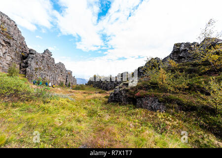 Thingvellir National Park grass autumn plants during day landscape, people walking on canyon trail in Iceland, Golden circle route - Stock Photo