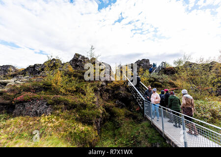 Thingvellir, Iceland - September 20, 2018: National Park autumn plants during day landscape, people walking on canyon trail of Golden circle route - Stock Photo