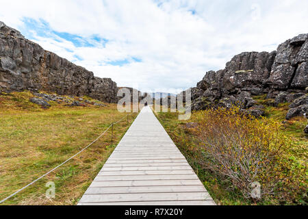 Thingvellir, Iceland National Park canyon continental divide plate during day landscape, people walking on wooden trail boardwalk at Golden circle rou - Stock Photo