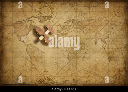 Small wood airplane over world nautical map as travel, explore and communication concept - Stock Photo