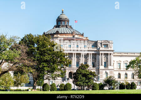 US National Library of Congress dome exterior with American flag waving in Washington DC, USA on Capital capitol hill, columns, facade landscape build