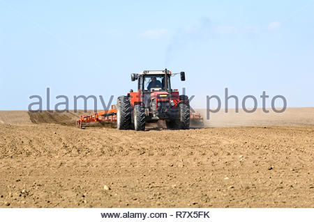 Tractor prepares spring field for seeding. Driver in cabine. - Stock Photo