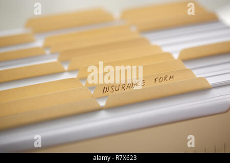 Yellow folders with labels and paper in a row - Stock Photo
