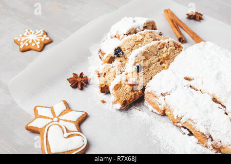 Traditional Christmas stollen with gingerbread, cinnamon, anise stars on grey wooden table. Shot at angle. - Stock Photo