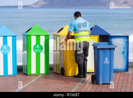 Council worker emptying colour coded waste bins for recycling plastic, paper, organic...on beach in Spain - Stock Photo