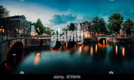Evening twilight panorama of Amterdam cityscape with canal, bridge and medieval houses in the evening illumination. Bridge over Keizersgracht (Emperor's canal) in Amsterdam, The Netherlands - Stock Photo