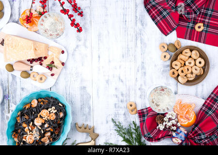 Christmas food in Italy for the holiday. Pasta is black with seafood and various snacks, wine and parmesan cheese. Top view and light wooden backgroun - Stock Photo