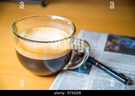 Cup of coffee, newspaper and a pen - Stock Photo