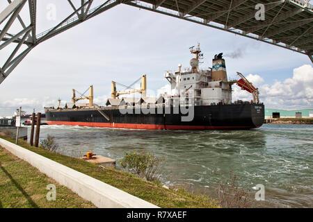 Cargo ship transporting grain, entering Port of Corpus Christi, passing under Harbor bridge. - Stock Photo