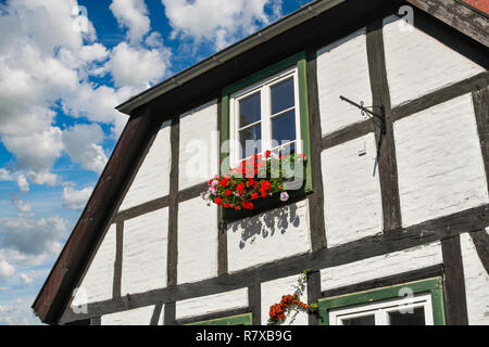 A typical Nordic or Scandinavian home with a colorful flowerbox outside it's window in the coastal medieval town of Warnemunde, Germany - Stock Photo
