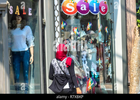 Cairo, Egypt - September 16, 2018: Arabian Woman with red hijab walking in front of a westernized shop, in Cairo, Egypt. - Stock Photo