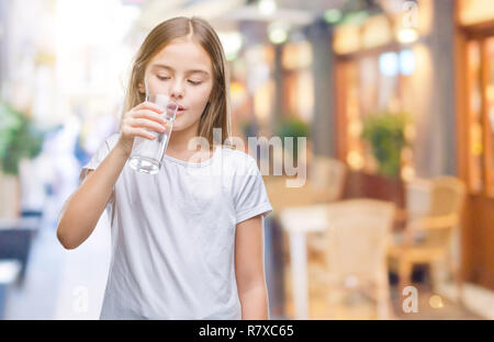 Young beautiful girl drinking glass of water over isolated background with a confident expression on smart face thinking serious - Stock Photo