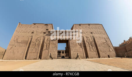 The main entrance of Edfu Temple showing the first pylon, Dedicated to the Falcon God Horus, Located on the west bank of the Nile, Edfu, Upper Egypt - Stock Photo
