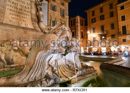 Closeup of the Pantheon Fountain or Fontana del Pantheon in the Piazza della Rotonda at night with sidewalk cafes and shops illuminated in Rome Italy - Stock Photo
