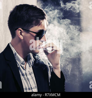 Young handsome man in sunglasses smoking a cigarette in city street Stylish fashion male model in black blazer - Stock Photo
