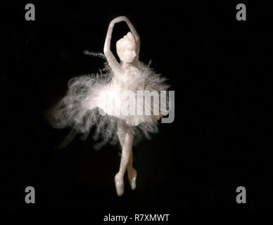 A beautiful white hanging ballerina with feathers against a dark background - Stock Photo
