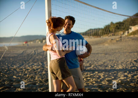 Mid-adult couple playing volleyball on a beach. - Stock Photo