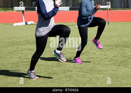 Two high school girls do A-Skips during track and field practice - Stock Photo